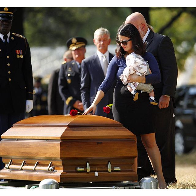 Meghan Florich, holding her newborn baby, places a rose on her husband Staff Sgt. Thomas Florich III's casket during a burial service at Arlington National Cemetery. (Mike Morones/Army Times)