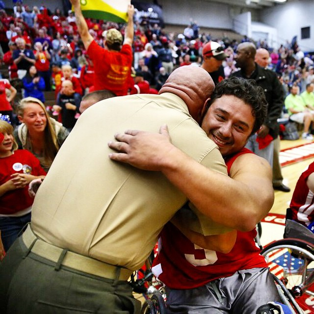 Col. Shane Tomko hugs Marine Corps athlete Eric Cervantes following the Marines' win over Army for the gold medal in wheelchair basketball at