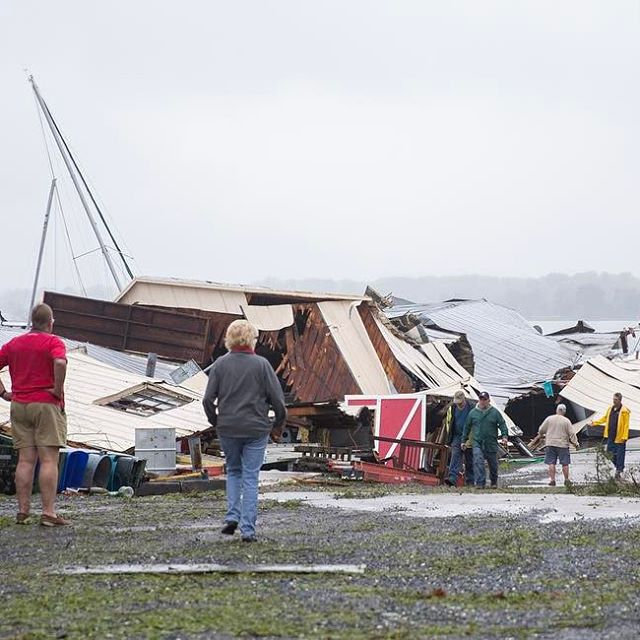 Bystanders watch as workers assess the damage at Boathouse Marina in Colonial Brach, Va. on April 22, 2017. A severe storm knocked trees down, caused property damage and disrupted electricity. (Mike Morones / The Free Lance-Star)