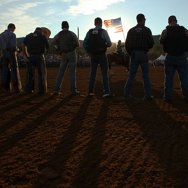 Cowboys listen to the Star Spangled Banner before the start of the monthly rodeo at Oakland Heights Farm