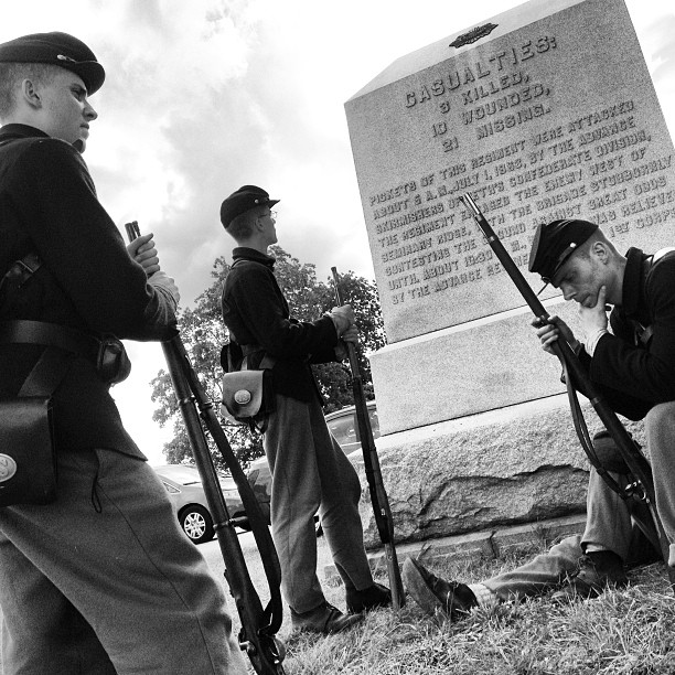 Reenactors rest in the shade of the 8th New York Cavalry Regiment monument along McPherson Ridge in Gettysburg
