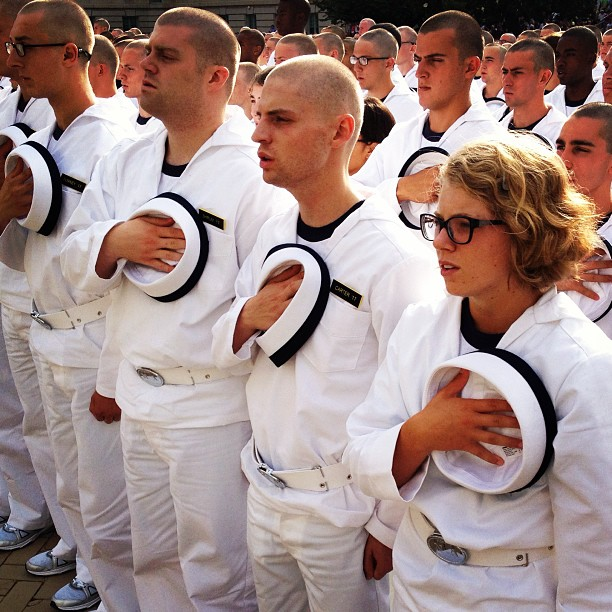Plebes stand during the singing of Navy Blue & Gold after taking the oath of office at the Naval Academy.