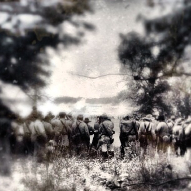 Confederate reenactors wait in the treeline before participating in a reenactment of Pickett's Charge.